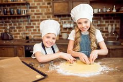 Kids in chef hats making shaped cookies in kitchen Royalty Free Stock Photography