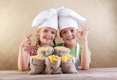 Kids with chef hats and pasta varieties Royalty Free Stock Photos