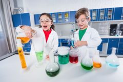 Kids in chemical lab. Excited kids in lab coats and protective glasses making experiment in chemical laboratory stock photography