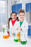 Kids in chemical lab. Happy kids in lab coats posing in chemical laboratory and smiling at camera Stock Image