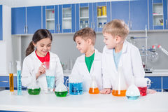 Kids in chemical lab. Three smiling kids in lab coats making experiment in chemical laboratory royalty free stock photography