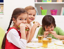 Kids chomping on sandwiches Stock Photography