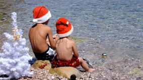 Kids in chrismas hat are playing with chrismas attribbute on the beach stock video footage