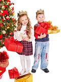 Kids with Christmas gift box. Children in crown with gift box near Christmas tree. Isolated Stock Photo
