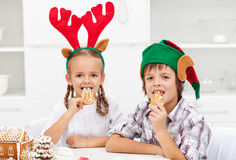 Kids with christmas hats eating gingerbread cookies Stock Photo