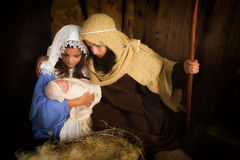 Kids christmas play. Christmas nativity scene reenacted by children and a doll Royalty Free Stock Photography