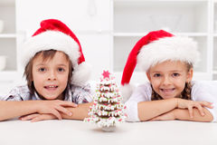 Kids at christmas time with gingerbread tree. Happy kids at christmas time with a gingerbread tree they decorated Stock Image