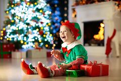 Kids at Christmas tree. Children open presents. Child opening present at Christmas tree at home. Kid in elf costume with Xmas gifts and toys. Little baby boy stock photography