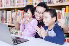 Kids clapping hands with teacher in library Royalty Free Stock Photo