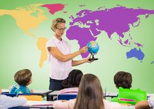 Kids in class with teacher holding globe in front of colorful world map Royalty Free Stock Photo