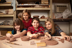Kids in a clay studio. Four cute kids posing in a clay studio royalty free stock image