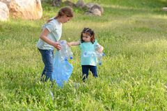 Kids cleaning in park.Volunteer children with a garbage bag cleaning up litter, putting plastic bottle in recycling bag. royalty free stock images