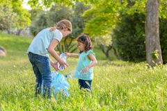 Kids cleaning in park.Volunteer children with a garbage bag cleaning up litter, putting plastic bottle in recycling bag. stock images