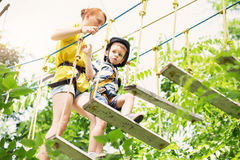 Kids climbing in adventure park. Boy enjoys climbing in the rope. S course adventure. Child climbing high wire park. Happy boys playing at adventure park Stock Photo