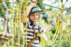 Kids climbing in adventure park. Boy enjoys climbing in the rope. S course adventure. Child climbing high wire park. Happy boys playing at adventure park Royalty Free Stock Photos