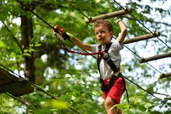 Kids climbing in adventure park. Boy enjoys climbing in the ropes course adventure Royalty Free Stock Photo