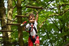 Kids climbing in adventure park. Boy enjoys climbing in the ropes course adventure. Child climbing high wire park. Happy boys playing at adventure park holding Royalty Free Stock Photos