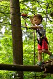 Kids climbing in adventure park. Boy enjoys climbing in the ropes course adventure Stock Images