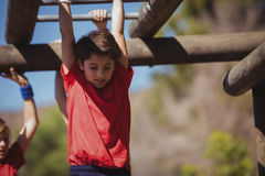 Kids climbing monkey bars during obstacle course training Stock Photo