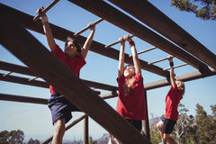 Kids climbing monkey bars during obstacle course training royalty free stock photos