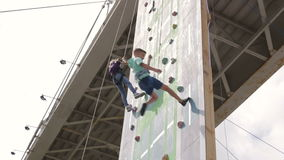 Kids climbing rock wall while climbing competition stock video