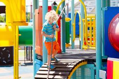 Kids on playground. Children play in summer park. Kids climbing and sliding on outdoor playground. Children play in sunny summer park. Activity and amusement Royalty Free Stock Images