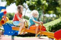 Kids on playground. Children play in summer park. Kids climbing and sliding on outdoor playground. Children play in sunny summer park. Activity and amusement Stock Photography