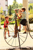 Kids climbing a vintage bicycle on the playground in the summer park Stock Photography