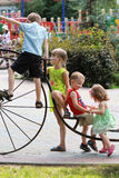 Kids climbing a vintage bicycle on the playground in the summer park Stock Photo