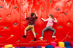 Kids climbing on a wall in attraction playground. Active kids climbing on a wall in childrens attraction playground. Entertainment center. Happy childhood royalty free stock image