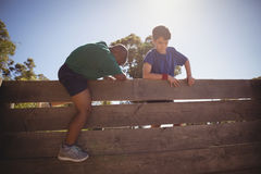 Kids climbing wooden wall during obstacle course stock image