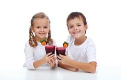 Kids clink glasses of fresh beetroot juice Stock Photo