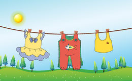 Kids clothes hanging under the sun Stock Photos