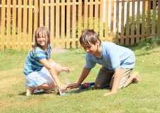 Kids in clothes playing with sprinkler Stock Photos