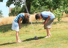 Kids in clothes playing with sprinkler Royalty Free Stock Photography