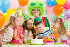 Kids with clown celebrating birthday party. And blowing candle on cake Stock Image