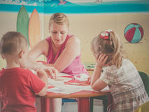 Kids club activities. Woman and children drawing pictures during art time at the nursery Stock Photography