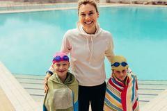 Kids with coach at swimming pool. Children wrapped in towel standing with a women trainer by the pool. Girl and boy with coach at swimming pool stock image