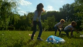 Kids collecting empty plastic bottle while cleaning outdoors