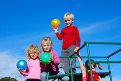 Kids with colorful balls. A group of caucasian children standing on a jungle gym with colorful balls in their hands and playing on the playground outdoors in Stock Photo