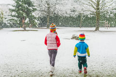 Kids in colorful clothes walking in a park under snowfall Royalty Free Stock Photography