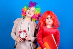 Kids colorful curly wig clown style hold alarm clock. I am not joking about discipline. School alarm. Girl worry about. Time. Discipline and time concept stock photos