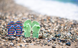 Kids colorful flip flops on beach in front of the Stock Images