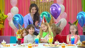 Kids in colorful hats celebrating birthday with mother and fiends. Kids in colorful hats celebrating their birthday with mother and fiends at a children`s stock video