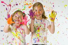 Kids in colorful paint. Two young girls with colorful finger paints Royalty Free Stock Photos