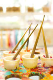 Kids colorful paint brushes for art. Kids paint brushes for art on splattered table Royalty Free Stock Images