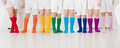 Kids with colorful socks. Children footwear. Kids wearing colorful rainbow socks. Children footwear collection. Variety of knitted knee high socks and tights Royalty Free Stock Photos