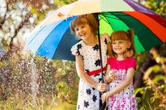 Kids with colorful umbrella playing in autumn shower rain. Little girls play in park by rainy weather. Fall outdoor fun for children. Kid catching rain drops stock photos