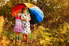 Kids with colorful umbrella playing in autumn shower rain. Little girls play in park by rainy weather. Fall outdoor fun for children. Kid catching rain drops royalty free stock images
