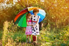 Kids with colorful umbrella playing in autumn shower rain. Little girls play in park by rainy weather. royalty free stock image